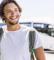 homem sorrindo com um ônibus ao fundo