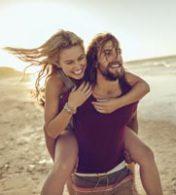 homem carregando mulher em suas costas com uma praia ao fundo