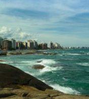 praia em espírito santo com uma cidade ao fundo