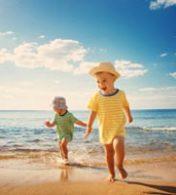 dois bebês sorrindo e caminhando na praia