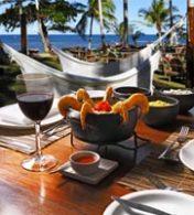 uma porção de camarão ao lado de uma taça de vinho e uma praia ao fundo