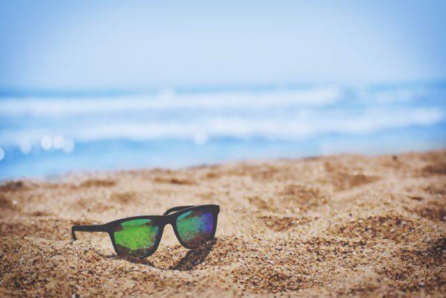 imagem de uma praia e um óculos de sol